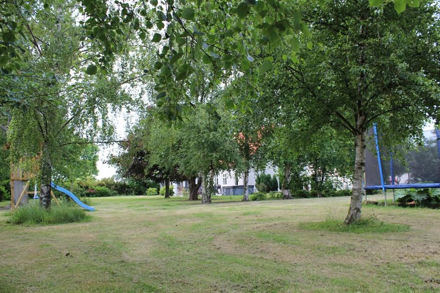 Have med legeområde og hus i baggrunden